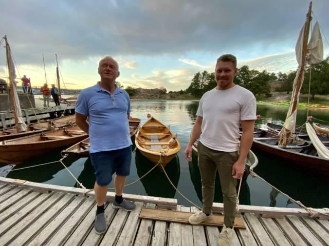 """Lokale filmstjerner! Båtbygger Svein Walvick og lærling Jonathan Grimstad foran """"Høvdingen"""" - sørlandssjekten de har bygget sammen. Foto: Forbundet KYSTEN"""